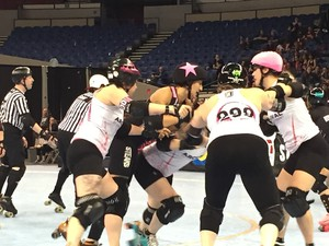The London Rollergirls jammer (in black, with pink star on helmet) attempts to break through the Arch Rival Roller Derby blockers at Veterans Memorial Coliseum, during the WFTDA championships.