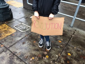 """A seventh grader at Metropolitan Learning Center holds a sign reading """"Revolution"""" during the Portland Public Schools student walkout, November 14 2016."""