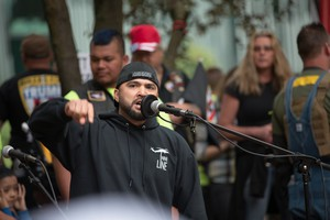 Joey Gibson, the Vancouver, Washington, resident who organized a June Trump Free Speech Rally in Portland addresses the crowd. Gibson held a moment of silence for the victims of the MAX train stabbings.