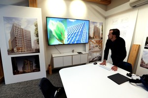 Lever Architecture founder Thomas Robinson looks over artist renderings of a 12-story all-wood building that his firm is working on to be built in Portland's Pearl District.