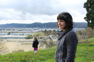 North Portland resident Stacey Schroeder stands on the bluff along WIllamette Boulevard overlooking Swan Island and the Daimler Trucks North America plant, as her daughter picks dandelions in the distance. Schroeder and other neighborsblame Daimler for paint odors in their neighborhood, and they blame the Oregon Department of Environmental Quality for failing to fix it.