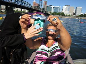 Costume designer Lisa Taylor helps her friend try and get a good picture of the solar eclipse on a dock in downtown Portland.