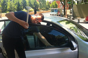Portland State University researcher Jackson Voelkel attaches a thermometer to a car window.