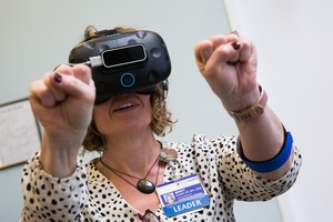 Clinic supervisor Mary Hlady collected virtual fireflies in her hands during a VR for pain management demo at Providence Gresham Rehab and Sports Therapy clinic.