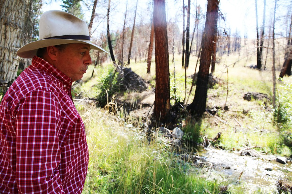 Gordon Larson watches a stream go by on his Grant County ranch.