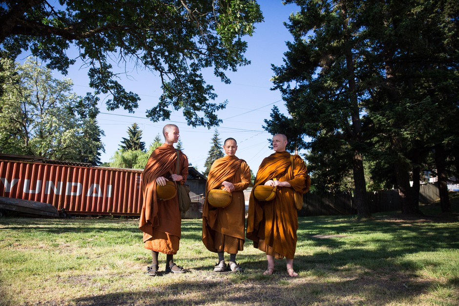 From left, Tan Sampanno, Ajahn Kassapo and Ajahn Sudanto make their morning alms round through White Salmon.