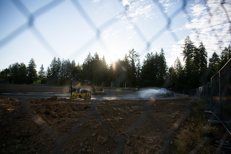 Workers install a new oblong track behind the Vernonia school building.