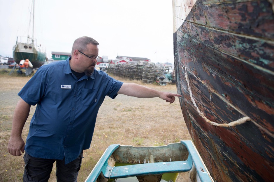 "Troy Wood, derelict vessel removal program manager for the state Department of Natural Resources, points out damage on an aging wooden-hulled vessel that could be a ""future customer"" of a boat recycling center in Ilwaco, Washington."