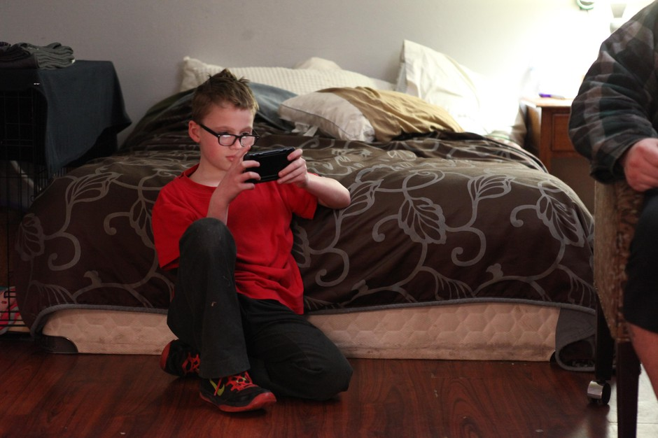 Talin, 10, plays with a smartphone while his parents talk at the Portland Value Inn in March 2018.