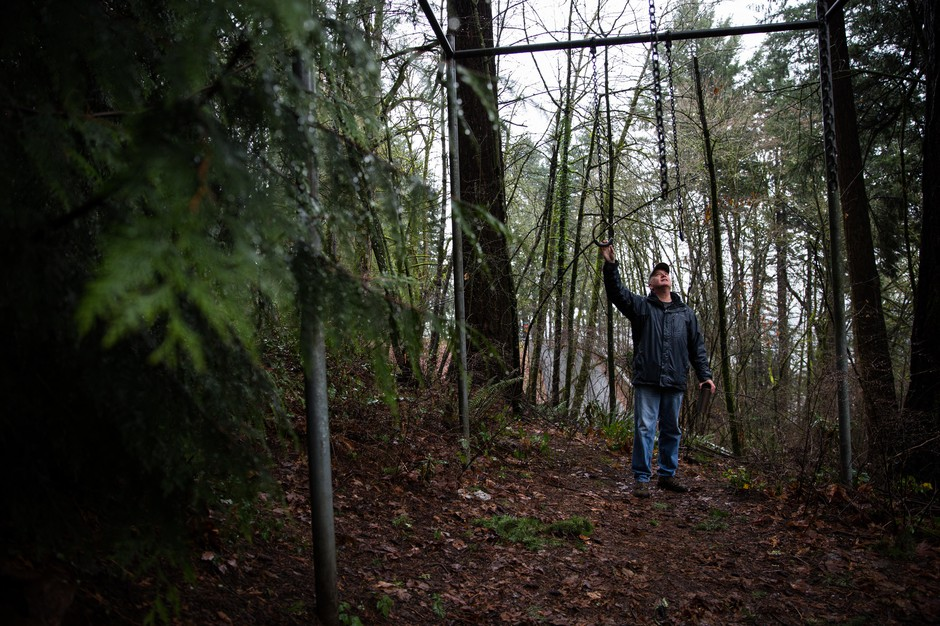 Wes Risher stands next to gymnastics rings on the Portland Exercise Course, an abandoned parcourse in Southwest Portland, Ore., Sunday, Jan. 20, 2019.