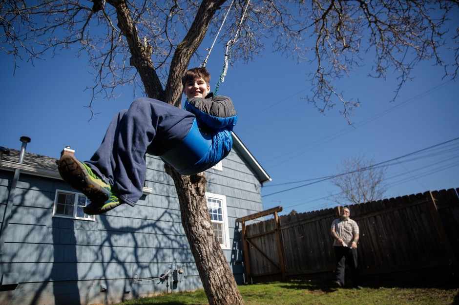 Colin, 12, swings in the backyard of his family home in Vancouver, Wa., while his father, Adam Bailey, pushes him on Saturday, March 2, 2019. The repetitive action of swinging helps Colin, who has autism, calm down.