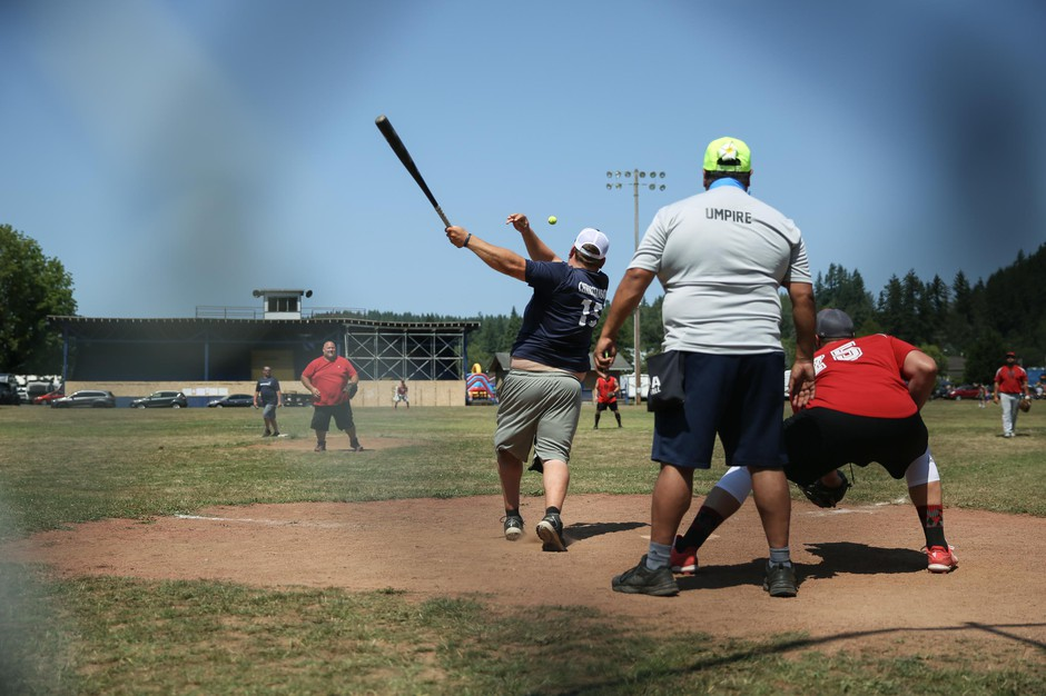 A player smacks a softball toward right field during a slow-pitch tournament at the Friendship Jamboree in Vernonia, Ore., Saturday, Aug. 3, 2019, the Greenman Field grandstands in the background. Activists see the Friendship Jamboree as a key event in the future of the grandstands.