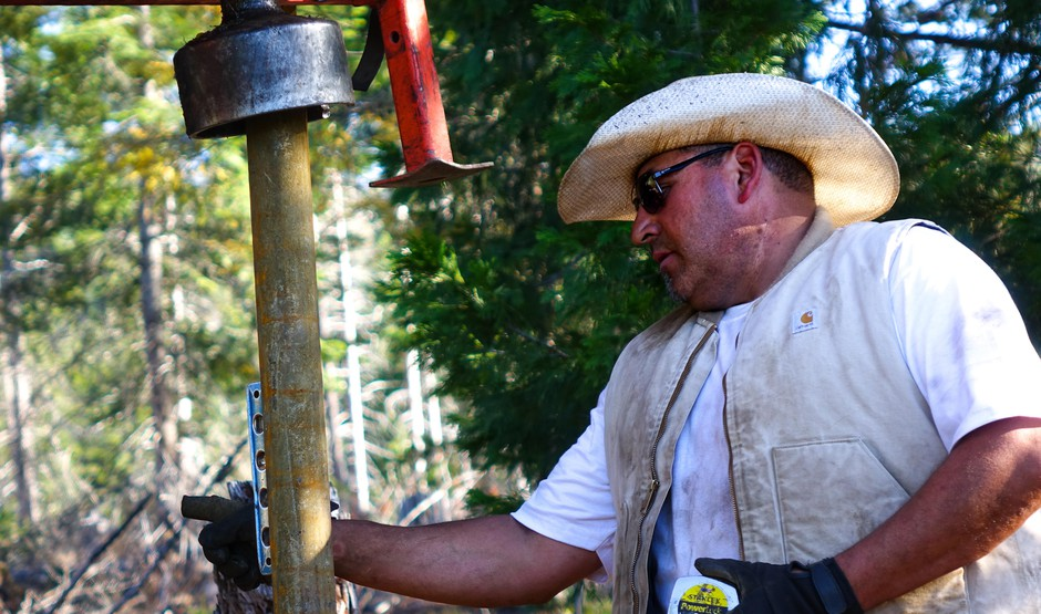 Pedro Ibarra ensures a post for Mill-Mar Ranch's new wolf fence goes in straight.