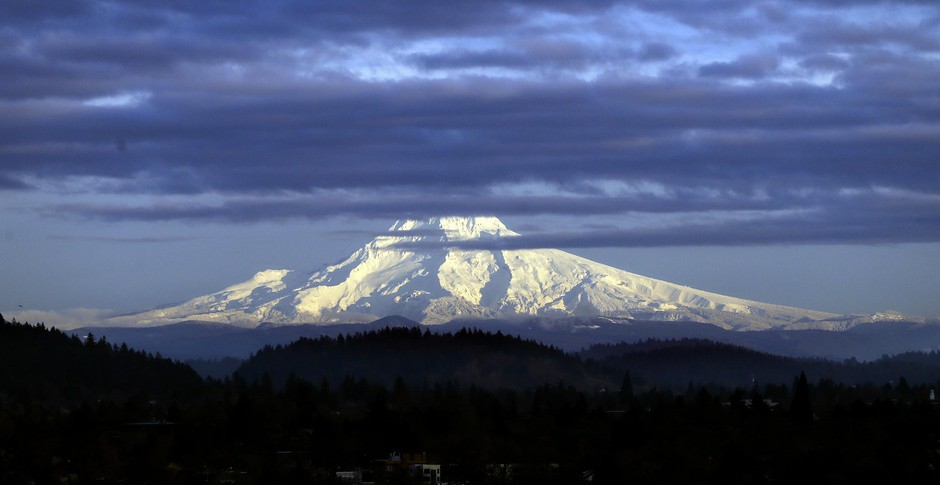 Oregon's Mount Hood, sporting a fresh coat of new snow, is lit through dispersing clouds by the setting sun as seen from Portland, Ore.