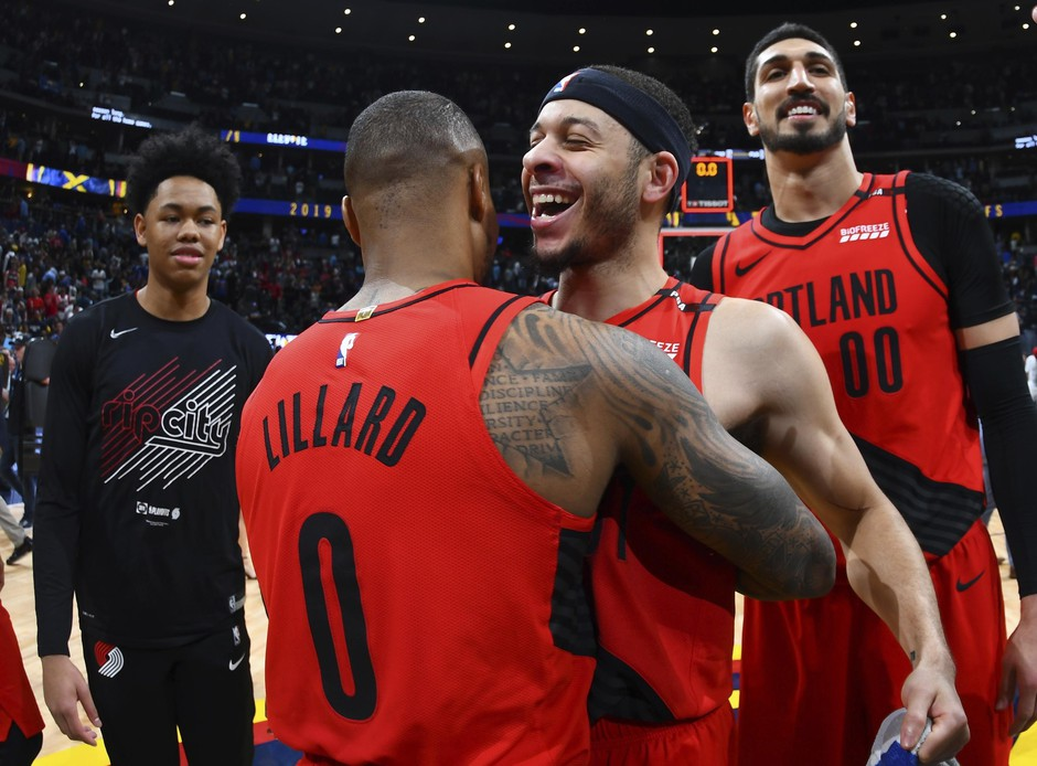 Portland Trail Blazers guard Damian Lillard celebrates with guard Seth Curry and center Enes Kanter after the second half of Game 7 of an NBA basketball second-round playoff series Sunday, May 12, 2019, in Denver.
