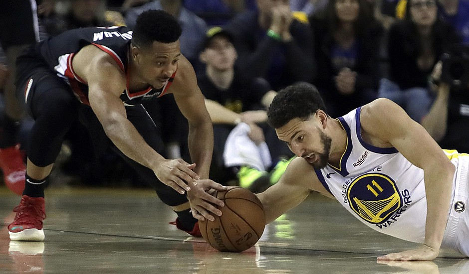 Portland Trail Blazers' CJ McCollum, left, and Golden State Warriors' Klay Thompson reach for the ball during the first half of Game 1 of the NBA basketball playoffs Western Conference finals Tuesday, May 14, 2019, in Oakland, Calif.