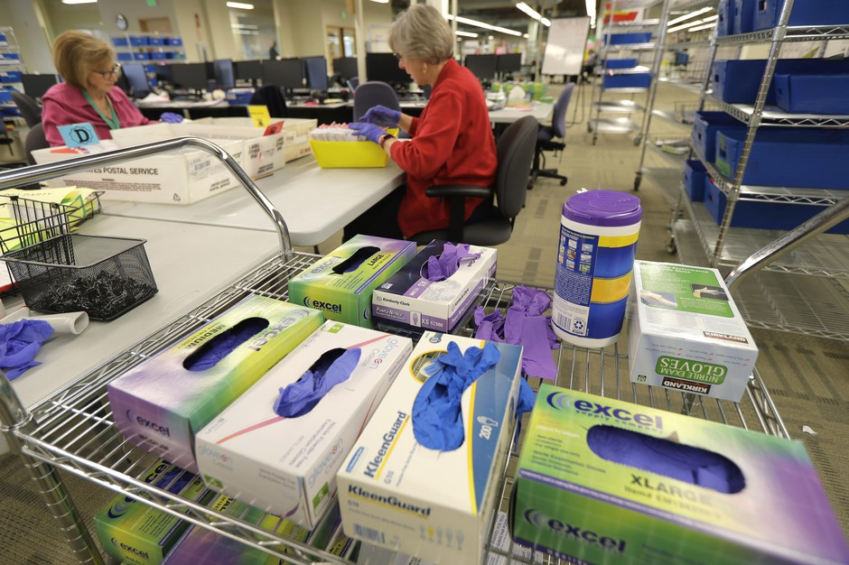 Boxes of gloves and a container of disinfecting wipes are staged near where workers handle ballots from the Washington state primary election, Tuesday, March 10, 2020, at the King County Elections headquarters in Renton, Wash.