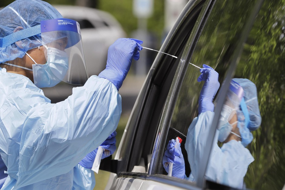 Medical assistant Melanie Zamudio is reflected in the window of a car as she reaches in to take a nasal swab from a driver at a drive-up coronavirus testing site Wednesday, April 29, 2020, in Seattle. The site, open Wednesdays and Saturdays from 10 a.m. to 3 p.m. in the Rainier Beach neighborhood, is available to anyone displaying the virus symptoms, are pregnant, over 60 or have a chronic condition, as well as health care workers and first responders.