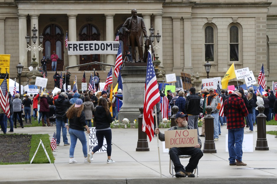 Protesters rally at the State Capitol in Lansing, Mich., Thursday, April 30, 2020. Hoisting American flags and handmade signs, protesters returned to the state Capitol to denounce Gov. Gretchen Whitmer's stay-home order and business restrictions due to COVID-19 while lawmakers met to consider extending her emergency declaration hours before it expires.
