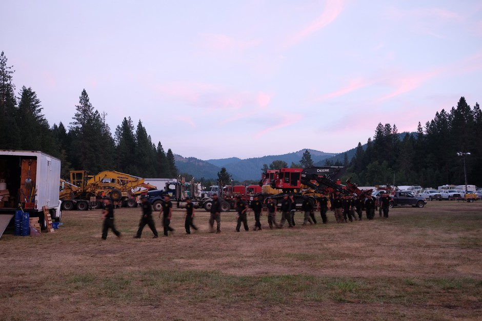 Firefighters are trained to walk in a line when out in the field. They keep that training in camp. Here, a team that has been working on the fire all day walks towards the food tent for dinner.