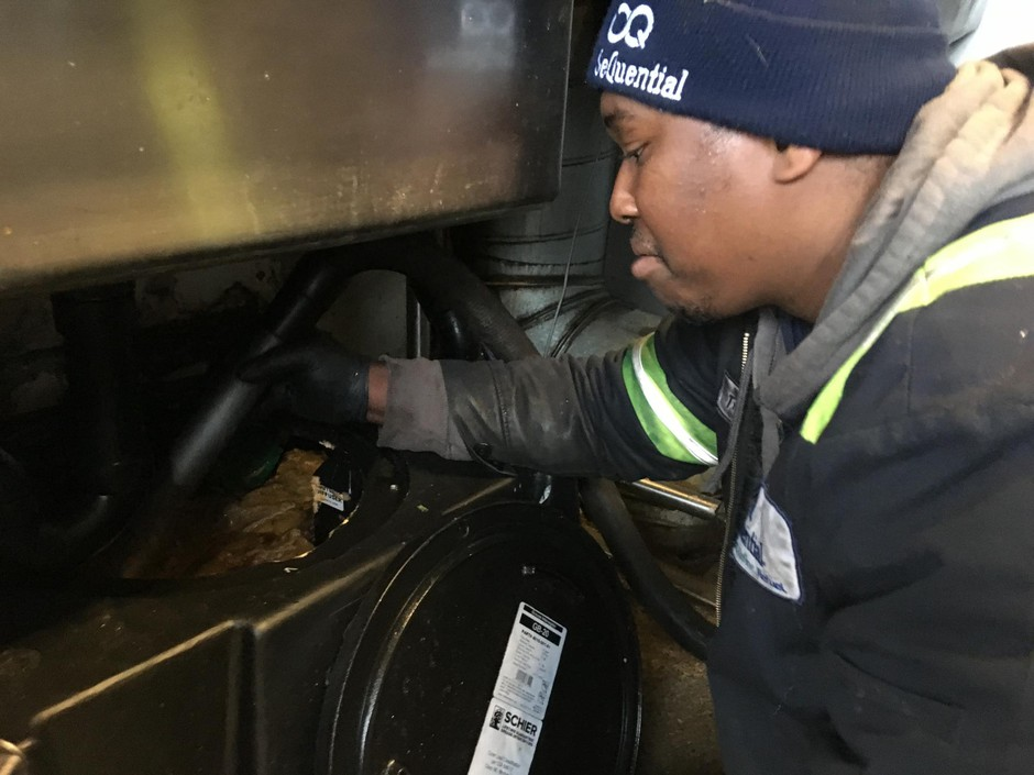 Trevor Bennett with Sequential Biofuels cleans out a grease trap at a brewery kitchen in Northeast Portland.