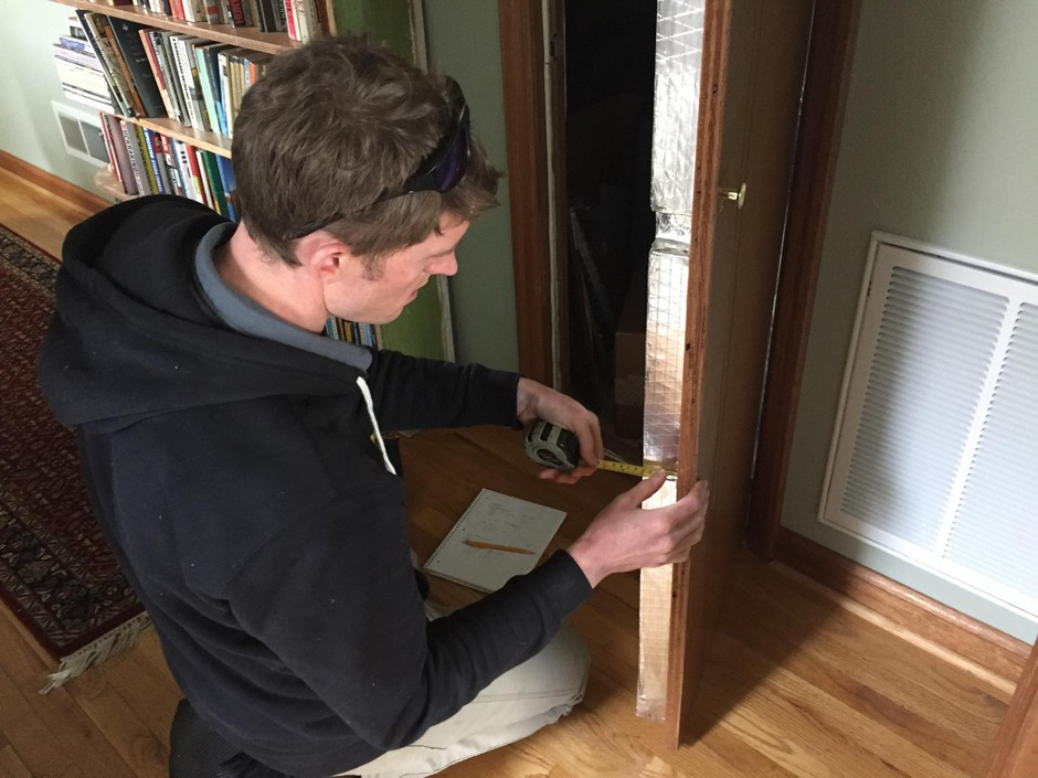 Peter Kernan of Enhabit measures the thickness of the insulation behind a wall as part of the home energy scoring process.