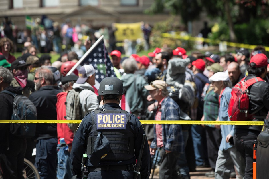 A police officer watches the crowd at a pro-Trump free speech rally in Portland, Oregon, Sunday, June 4, 2017.