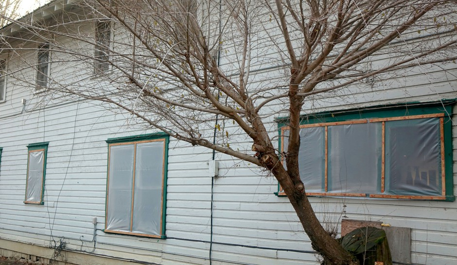 Plastic window covers or worker housing in Southern Oregon aims to prevent drafts.