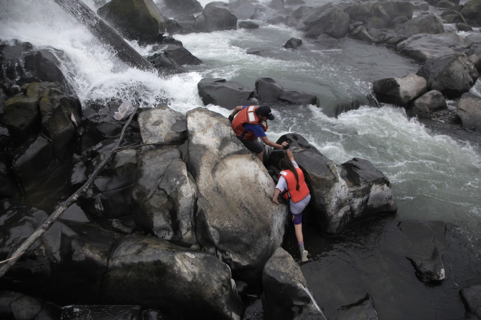 The upcoming generation of lamprey harvesters. Henry Begay helps his younger sister, Jackie, scale the slippery rocks at the base of Willamette Falls.