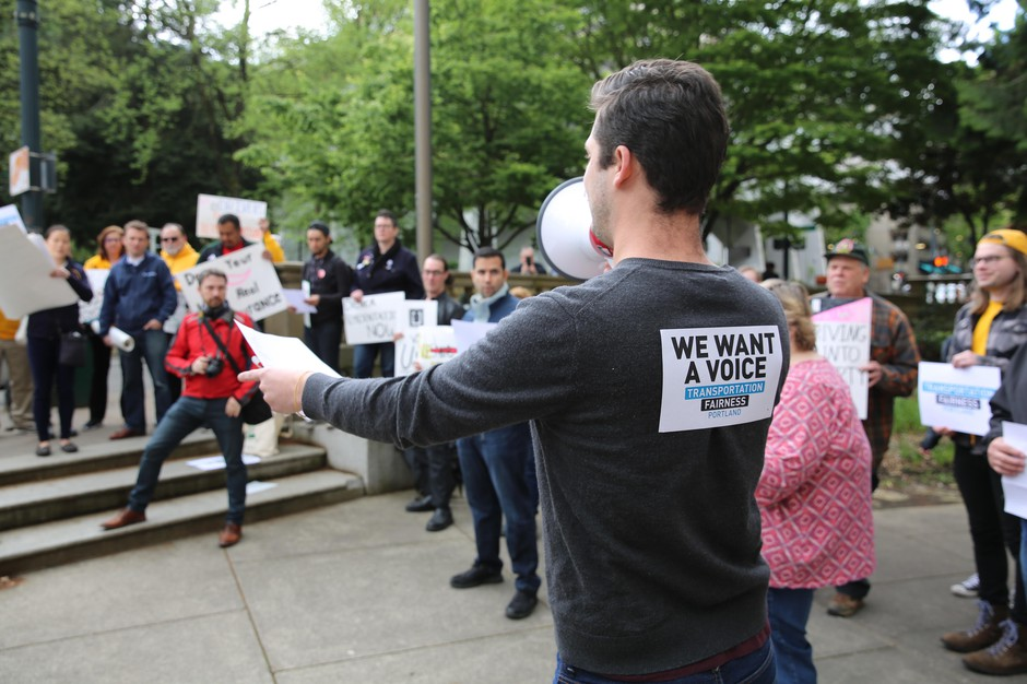 Full-time PSU student Owen Christofferson rallies a crowd of ride-hailing drivers outside Portland City Hall. He say Uber and Lyft have gradually reduced his wages. He now makes about minimum wage, despite working 15 to 40 hours a week.