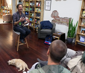 Jon Raymond speaking to a crowd and the house cat, Amber, at JaxDox Cafe & Books.