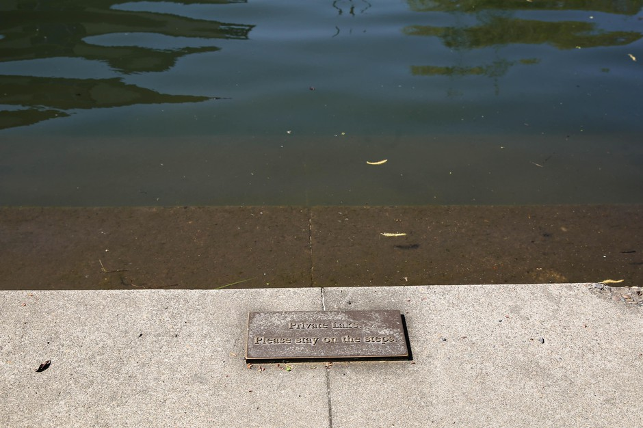 """Small metal signs adorn steps leading down to Oswego Lake's shore in a public park read: """"Private Lake – Please stay on the steps."""" Access to Oswego Lake is restricted to city residents only."""