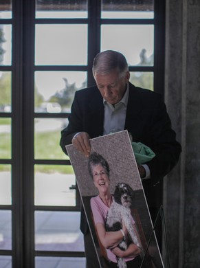 Bob Campbell carries his sister Linda's remains and portrait on his way to her gravesite.